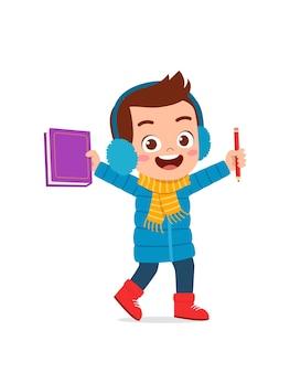 Счастливый милый маленький ребенок учится и надевает куртку в зимний сезон