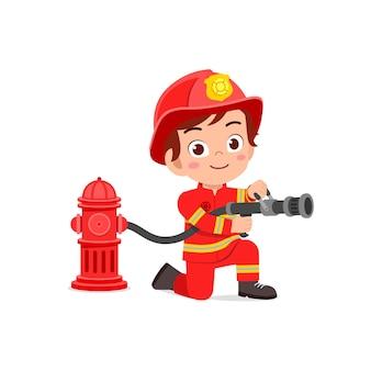 Счастливый милый маленький ребенок в форме пожарного и держит шланг