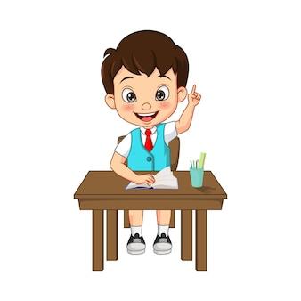 彼の手を上げる幸せなかわいい小さな学生の男の子