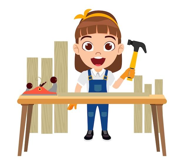 Счастливый милый умный ребенок плотник девушка персонаж стоящий молот рядом со столом с оборудованием и деревянными досками изолированы