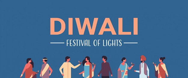 Happy diwali indian people group wearing national traditional clothes holding oil lamp banner