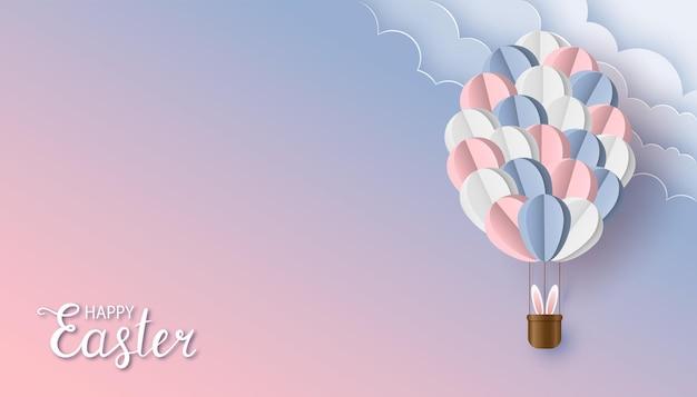 ペーパーカットスタイルのハッピーイースターの背景バニーの耳と雲と紙風船