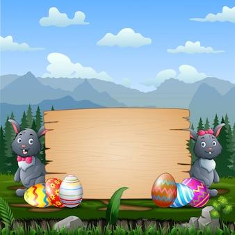 木製看板によるイースターエッグとハッピーイースターのウサギ