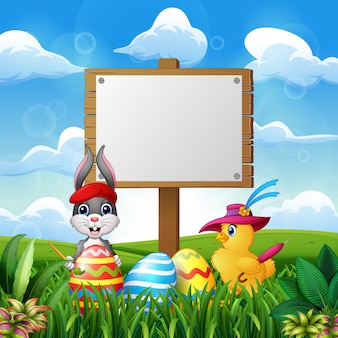 Happy easter bunny and chick with blank sign on the field
