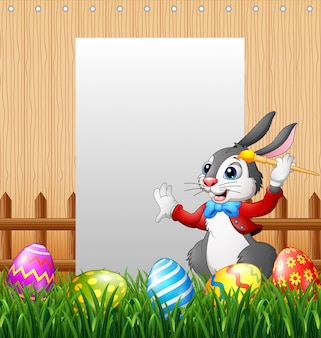 Happy easter bunny painting egg with blank sign background
