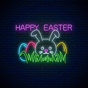 Happy easter glowing signboard with bunny and colored eggs on grass in neon style on dark brick wall background.