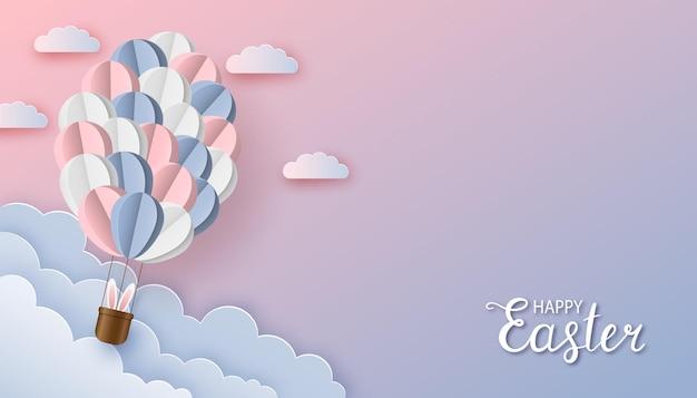 バニーの耳と雲と紙のカットスタイルの紙風船で幸せなイースター挨拶の背景 Premiumベクター