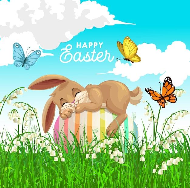 Плакат с праздником пасхи с милым кроликом, спящим на украшенном яйце на поле