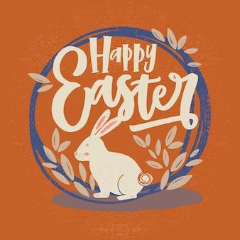 ハッピーイースターの碑文または休日の願いは、筆記体フォントとオレンジ色の背景の葉で飾られたラウンドフレームまたは花輪の中のバニーで書かれました。手描きイラスト