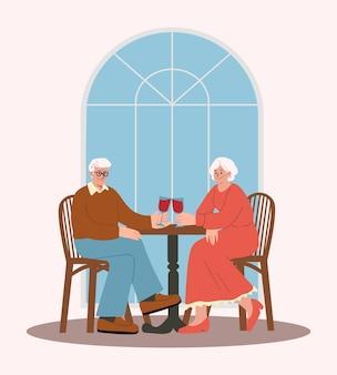 저녁 식사를 하고 레드 와인을 마시는 레스토랑에서 데이트를 하는 행복한 노부부