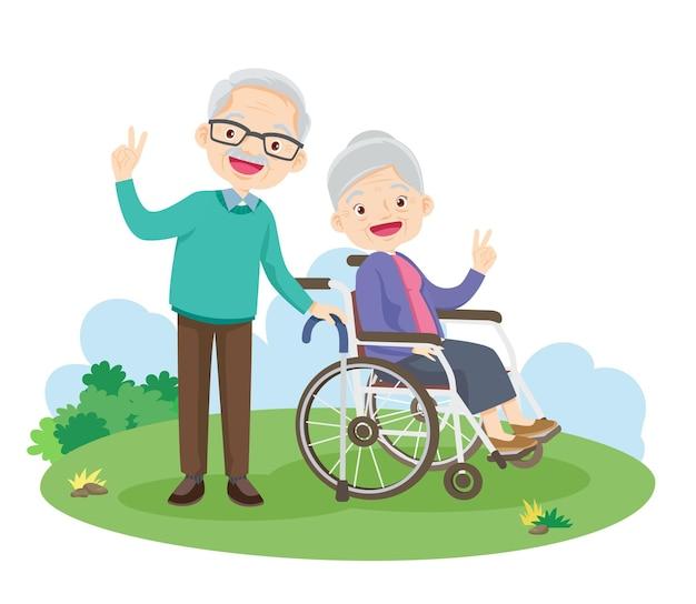 Счастливая пожилая рука победы жест, сидящая на инвалидной коляске в парке.