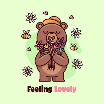 행복한 얼굴 갈색 곰이 서서 꽃 냄새를 맡습니다.