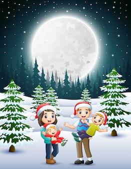 Счастливый familly в снежном саду ночью