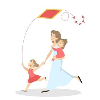 幸せな家族が楽しんでいます。赤ちゃんと子供を持つお母さんは凧と一緒に遊ぶ。夏のアクティビティ。図