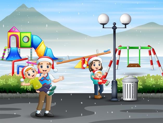 Happy family having fun at snowy playground