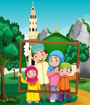 Famiglia felice che tiene la cornice per foto con moschea