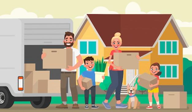 幸せな家族は新しい家に移動します。父、母、子供たちは家の背景に物を入れた箱を持っています
