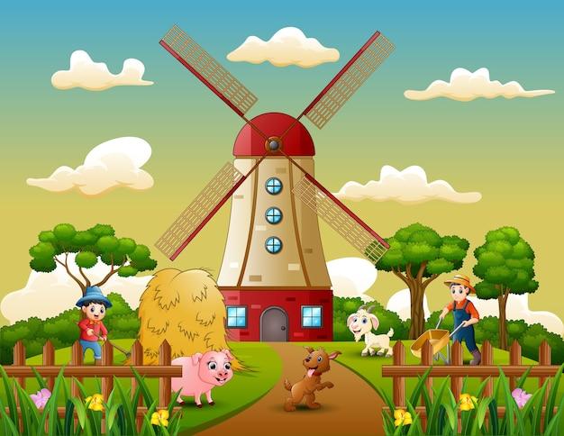 風車の建物の背景に動物と幸せな農夫