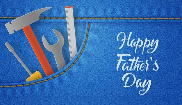 ツール、レンチ、ハンマー、ドライバーが付いたハッピー父の日カード。リアルなジーンズの背景。