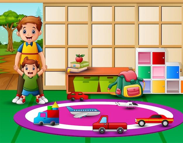 幼稚園のプレイルームで息子と一緒に幸せな父