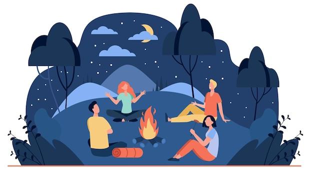 夏の夜のフラットイラストでキャンプファイヤーの近くに座っている幸せな友達。火の近くで怖い話をする漫画の人々