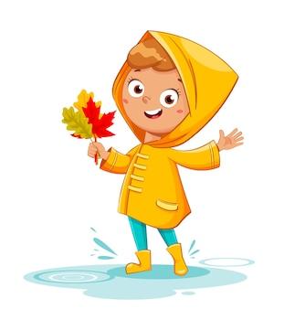 Счастливый смешной ребенок в желтом плаще и резиновых сапогах с листьями, дождливая осень