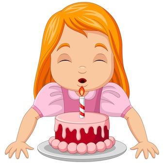 バースデーケーキのキャンドルを吹く幸せな女の子