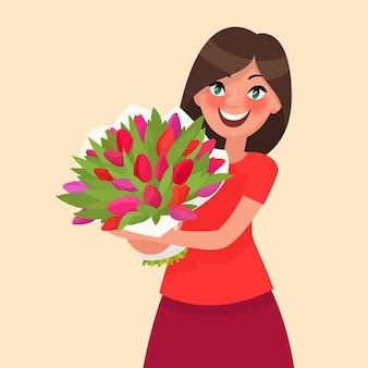 꽃의 꽃다발을 들고 행복 한 소녀입니다. 3 월 8 일 여성의 날 또는 생일을 축하합니다.