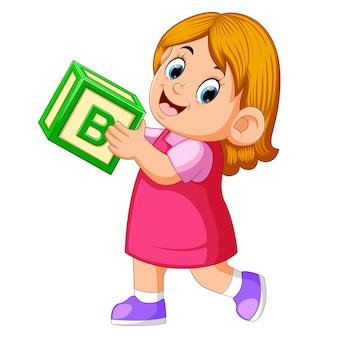 Счастливая девочка держит кубик алфавита