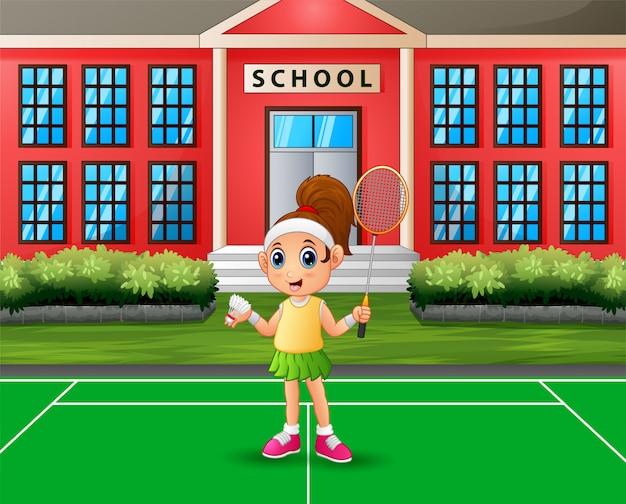 Счастливая девушка играет в бадминтон на школьной площадке