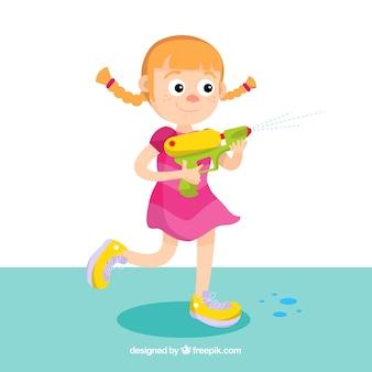 Ragazza felice che gioca con la pistola a acqua