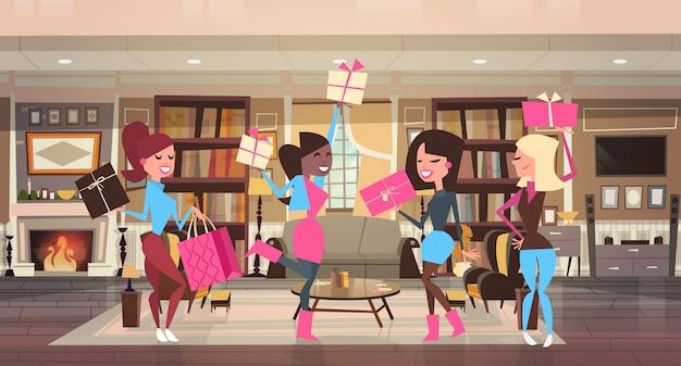 Счастливые девушки с подарочными коробками дома отмечают международный женский день 8 марта