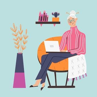 행복한 할머니는 노트북 컴퓨터의 의자에 앉아 있다