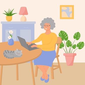 노트북을 든 행복한 할머니가 거실에 앉아 있다