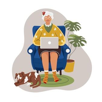 自宅のラップトップコンピューターで幸せな祖母。オンラインで働く老婆と犬は彼女の足元で眠る