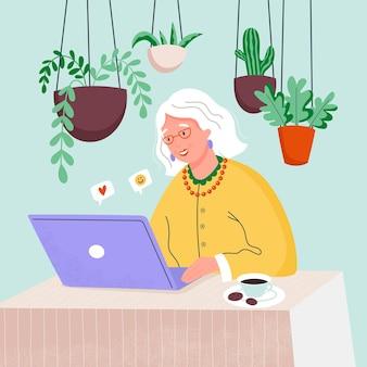 自宅のラップトップコンピューターで幸せな祖母。オンラインで働く老婆。