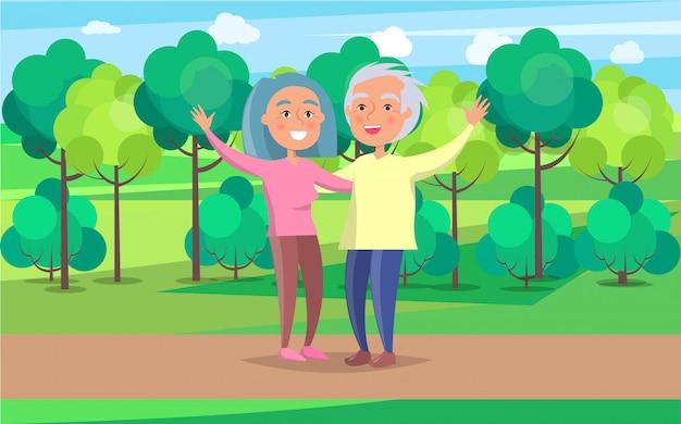 Happy grandparent senior couple wave hands in park