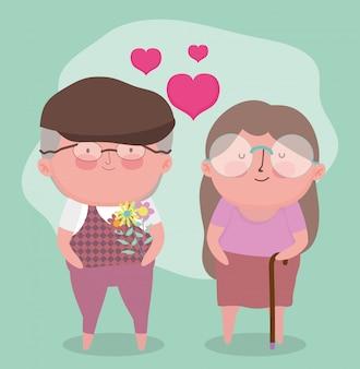 행복한 조부모의 날. 꽃과 산책 지팡이와 귀여운 노인 부부