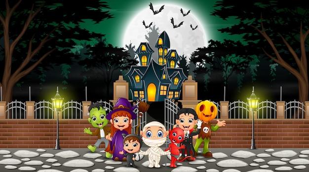 Счастливая группа хэллоуина празднует перед домом с привидениями