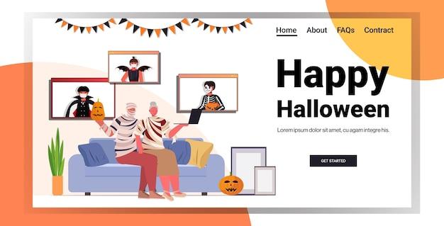 Счастливого хэллоуина, бабушка и дедушка в костюмах мумий обсуждают с детьми во время видеозвонка