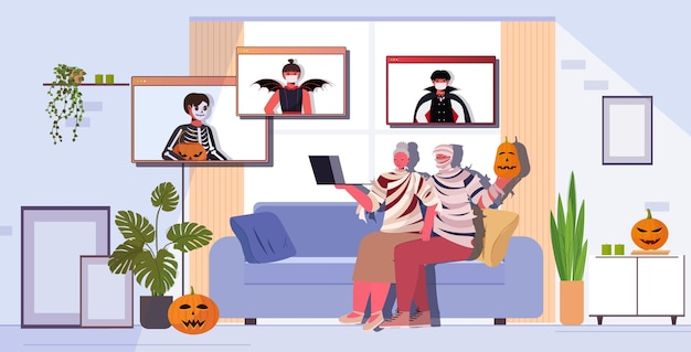 Happy halloween holiday celebration grandparents in mummy costumes discussing with children during video call living room interior