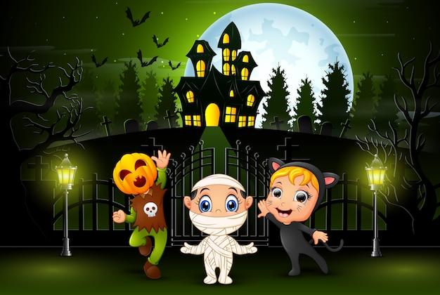Счастливый детей хэллоуин на открытом воздухе с фоном дома с привидениями