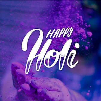 Happy holi lettering with hand and paint background