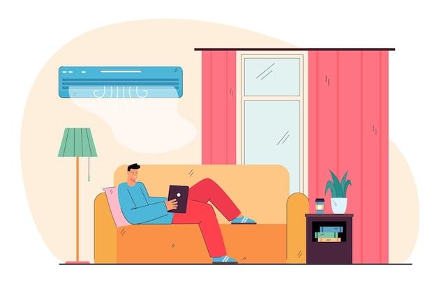 행복한 집 주인은 소파에 누워, 집에서 휴식을 취하고, 컨디셔너의 차가운 공기 아래에서 여가를 즐기고 있습니다.