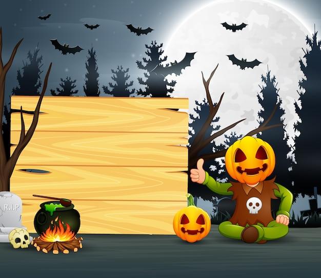 Happy kid wearing pumpkin mask costume sitting beside the wooden board