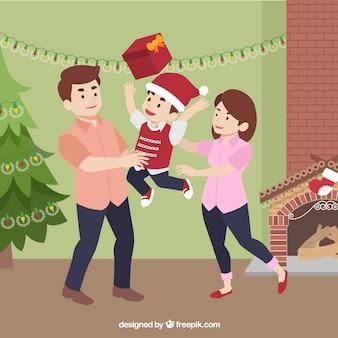 Bambino felice con il cappello della santa e regalo a giocare con i suoi genitori