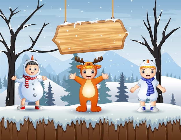 Happy kids in animal costume on snowy forest landscape