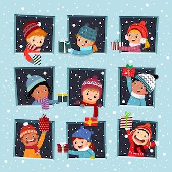Счастливые дети у окна делают рождественский подарок своему другу