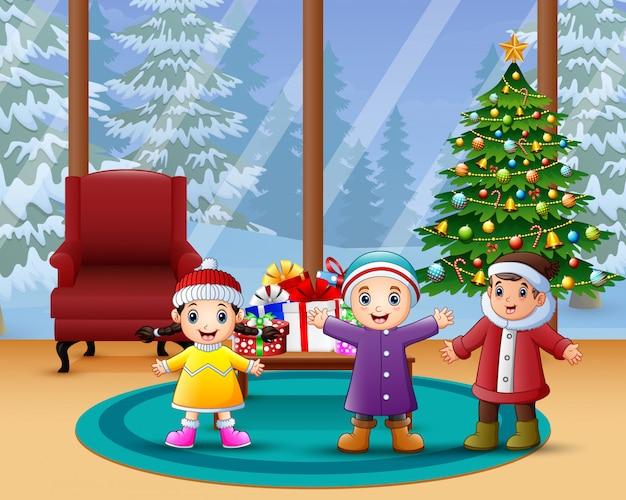 幸せな子供たちが家でクリスマスを祝う