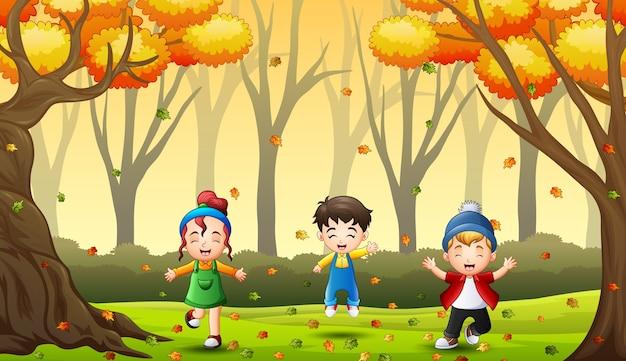 Счастливые дети веселятся и играют с осенними листьями в лесу